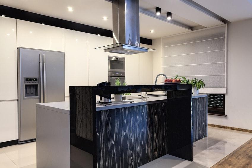 Weiße Küche mit Bar und Side by Side Kühlschrank im HIntergrund